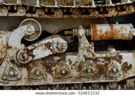 Rusty industrial machinery heavy equipment vehicle continuous track closeup.