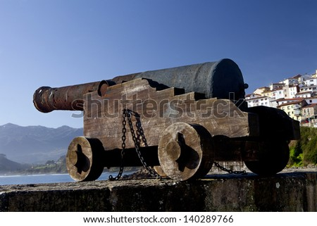 Rusty iron cannon pointing out to sea. Old Cannon. - stock photo