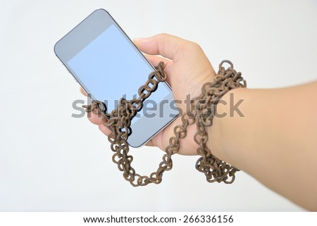 Rusty iron chain that ties together hand and smart phone in concept of social media and internet addiction - stock photo