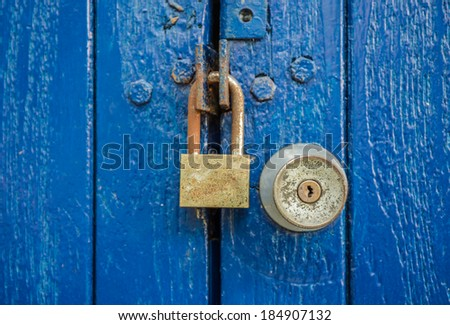 Rusty key and old knob on blue wood door - stock photo
