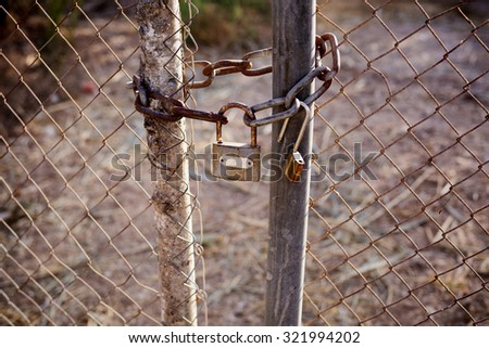 Rusty lock and chain locking the gates of the mesh netting - stock photo