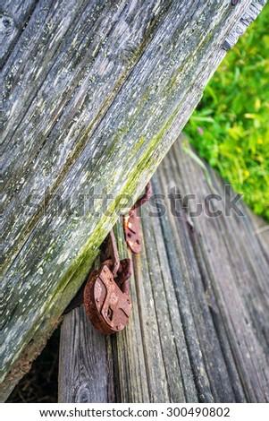 rusty lock on an old broken fence - stock photo