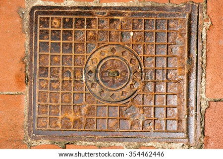 Rusty Manhole Cover / Metal brown rusty manhole cover on a pedestrian walkway - stock photo