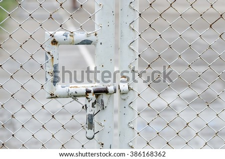 Rusty metal bolt on wire mesh door