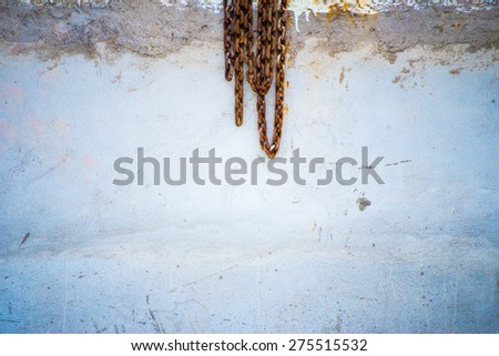 rusty metal chains concrete wall background - stock photo