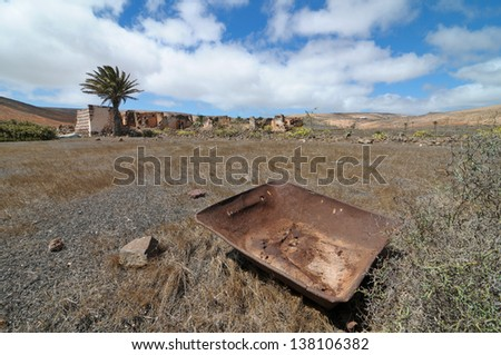 Rusty metal over a desert and a cloudy sky - stock photo