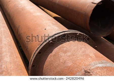 Rusty metal pipes stack on the construction site. - stock photo