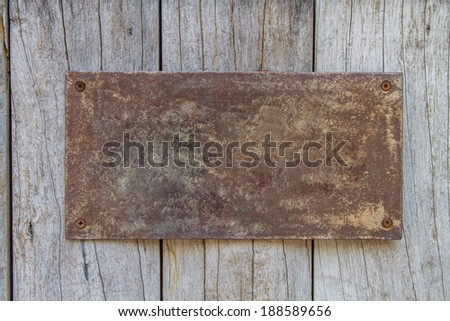 rusty metal plate on old wooden  - stock photo