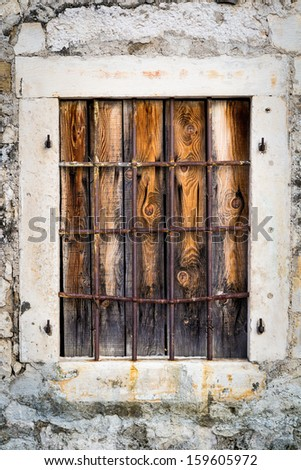 Rusty metal window with metal bars and wooden planks - stock photo