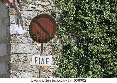 rusty no-parking road sign with written FINE in Italian - stock photo