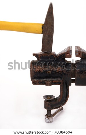 Rusty old bench vise and a hammer on a white background - stock photo