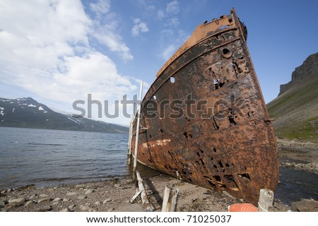 Rusty old  boat in Blue bay in Iceland - stock photo