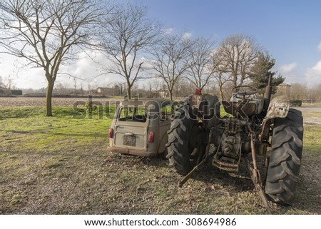 rusty old car and tractor in the nature - stock photo