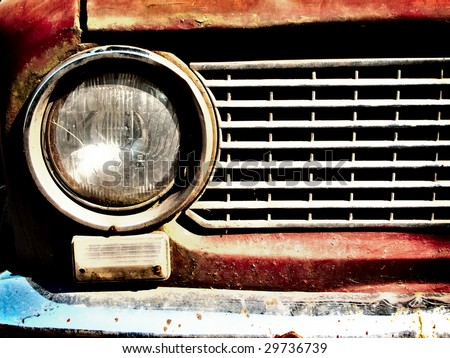 rusty old car light and bumper closeup - stock photo