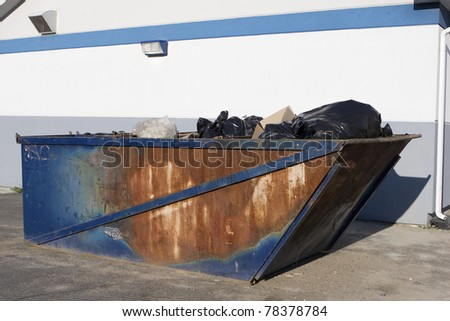 Rusty old dumpster behind convenience store - stock photo