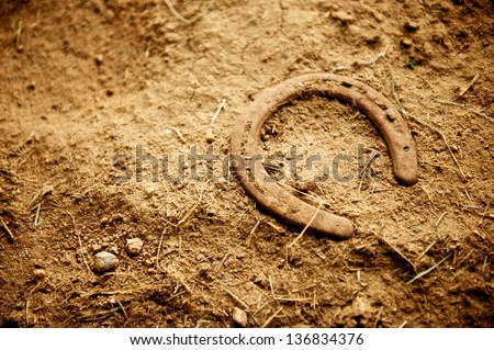 Rusty old horse shoe with a nail still in it lying alone on the dirt floor of an old barn - stock photo