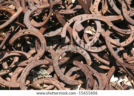 Rusty old horseshoes with nails on them background - stock photo