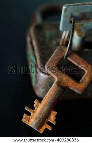 Rusty old key and lock on dark background - stock photo