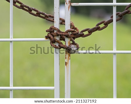 Rusty old metal chain locking a white gate entrance. Shallow depth of field with focus on chain. - stock photo
