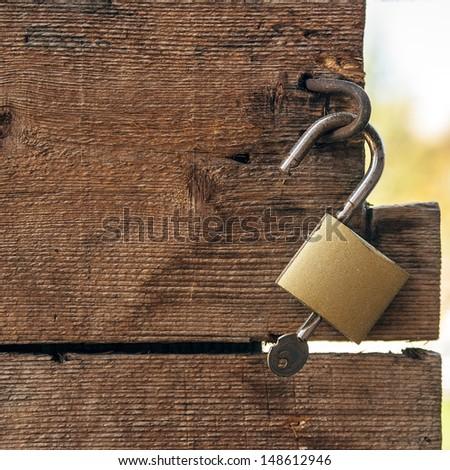 Rusty old metal padlock and modern padlock on an old wooden door. - stock photo