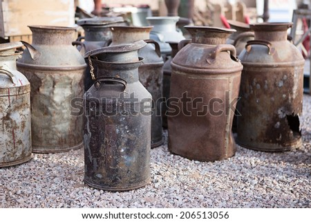 Rusty old milk cans at a flea market - stock photo