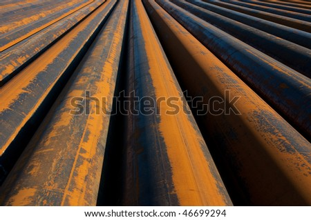 Rusty pipes waiting to be used - stock photo