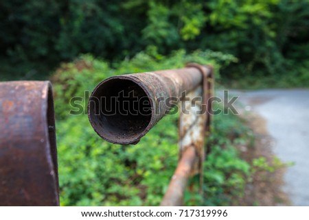 rusty railing pipe of a bridge in the countryside