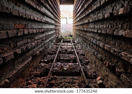 Rusty rails in the ruins of brick factory - stock photo