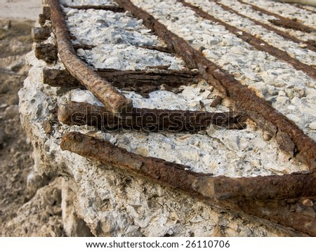 Rusty reinforcement rods in the crushed concrete slab - stock photo