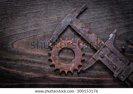 Rusty retro-styled measuring calipers with pinion gear on vintage dark wooden background construction concept. - stock photo