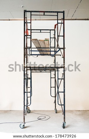 Rusty scaffold painting a white empty wall - stock photo