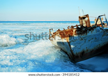 Rusty ship abandoned in the blue ice of Dnestrovskiy firth, Stouth Ukraine - stock photo