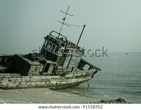 Rusty ship grounded at the beach - stock photo