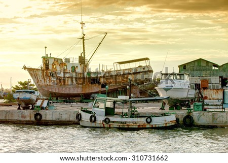Rusty ships and yachts on the dock - stock photo