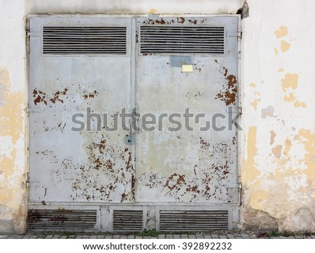 Rusty steel gate are painted with the bare burst gray paint - stock photo