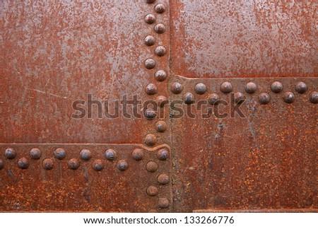 Rusty steel rivets on the steel sheet - stock photo