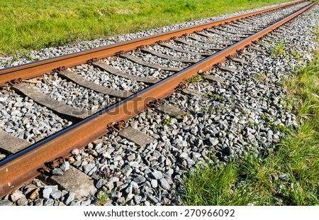 Rusty train tracks on a bed of concrete sleepers and pebbles - stock photo