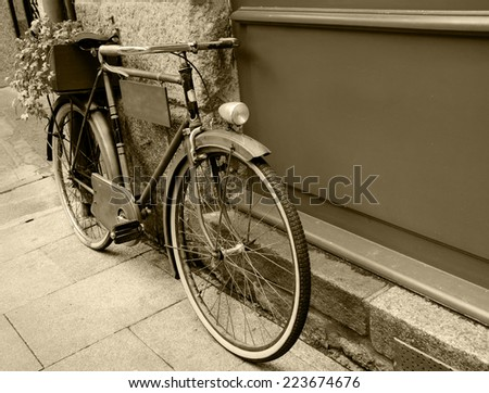 Rusty vintage bicycle leaning on  wooden board (useful for entering a text advertisement, menu etc) and carrying plants in wooden box as decoration. Aged photo. Sepia. - stock photo