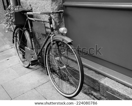 Rusty vintage bicycle leaning on  wooden board (useful for entering a text advertisement, menu etc) and carrying plants in wooden box as decoration. Aged photo. Black and white. - stock photo
