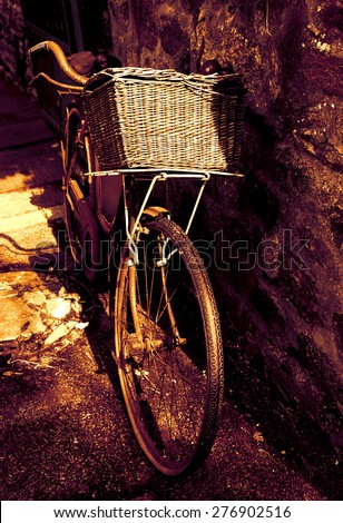 Rusty vintage bicycle with wicker basket leaning on a stone wall. Brittany, France. A game of light and shadow. Toned photo. - stock photo