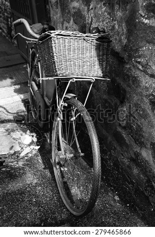 Rusty vintage bicycle with wicker basket leaning on a stone wall. Brittany, France. A game of light and shadow. Aged photo. Black and white. - stock photo