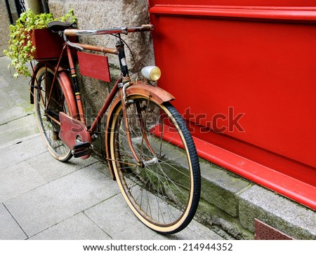 Rusty vintage red bicycle leaning with on red wooden board (useful for entering a text advertisement, menu etc) and carrying plants in wooden box as decoration.  - stock photo