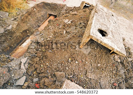 Rusty water pipe in trench and concrete construction on heap of earth