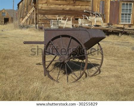 rusty wheel barrow in ghost town western - stock photo