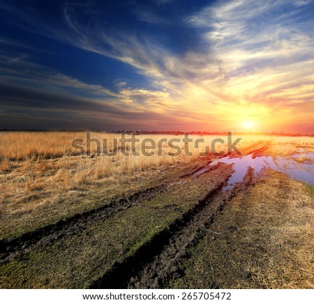 Rut dirt road across steppe after rain against sunset sky background - stock photo