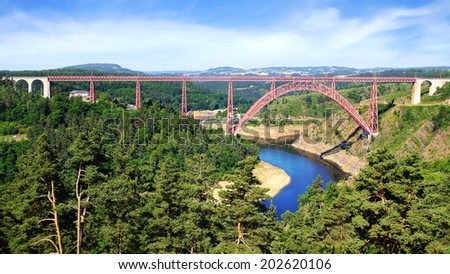 RUYNES-EN-MARGERIDE, CANTAL DEPARTMENT, FRANCE - JUNE 20, 2014: The Garabit Viaduct. The railway arch bridge through the River Truyere was constructed between 1882 and 1884 by Gustave Eiffel.   - stock photo
