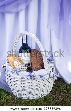 Rye bread and a bottle of wine in a basket on the grass