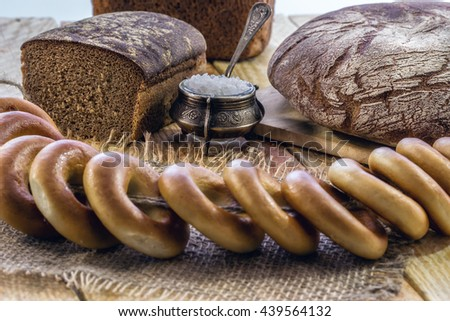 Rye bread and bagels on an old wooden table - stock photo