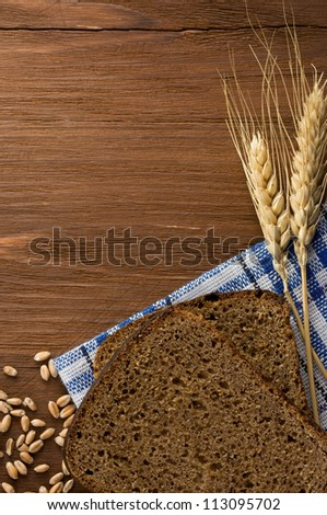 rye bread and ears of wheat on napkin - stock photo