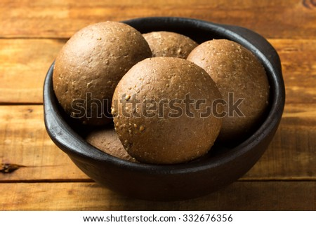 Rye bread in dark clay bowl on wooden background. Close up. Horizontal - stock photo